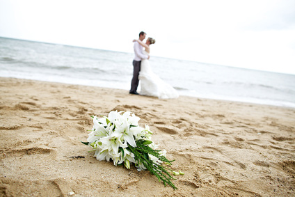 Beach wedding couple with bouquet of flowers on sand